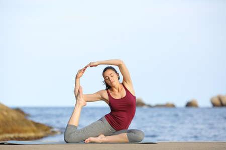Full body portrait of a woman practicing yoga pose on the beach Archivio Fotografico
