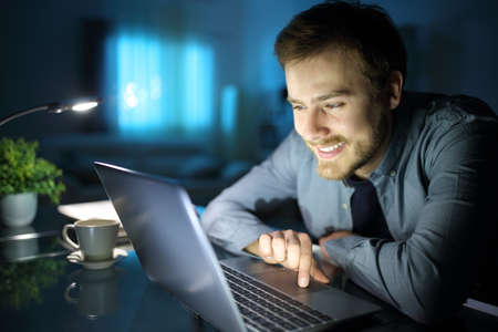 Happy man using laptop on a desk in the night at home Archivio Fotografico