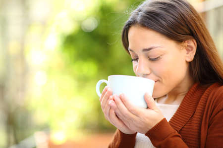 Relaxed woman drinking coffee in a green house garden Stock Photo