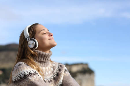Relaxed woman listening to music with wireless headphones breathing fresh air in nature Archivio Fotografico