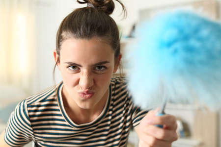 Front view portrait of a funny woman grimacing threatening at camera with a duster clean at home