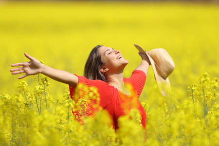 Happy woman celebrating vacation holding pamela stretching arms in a yellow field