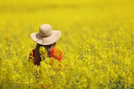 Back view of a woman wearing pamela walking through a yellow field in spring season
