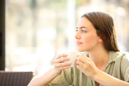 Relaxed woman drinking coffee from mug looking at side in a bar