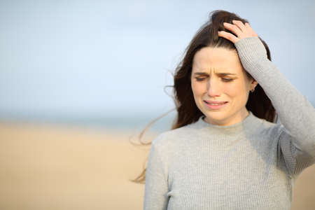 Sad woman walking alone crying on the beach