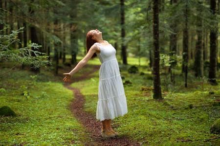 Woman in white dress celebrating vacation screaming in a green forest Imagens