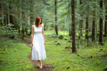 Front view portrait of a happy woman in white walking looking down in a green forest