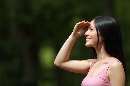 Side view portrait of a happy asian woman watching protecting from sun in a park