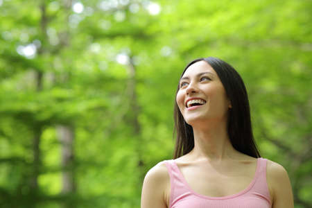 Amazed asian woman walking looking up and laughing in a forest Foto de archivo