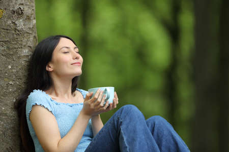 Happy asian woman drinking coffee relaxing breathing fresh air sitting in a forest