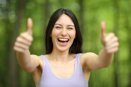 Front view portrait of an asian happy woman with thumbs up in a green forest