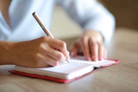 Close up of a woman hands writing on paper agenda in a table