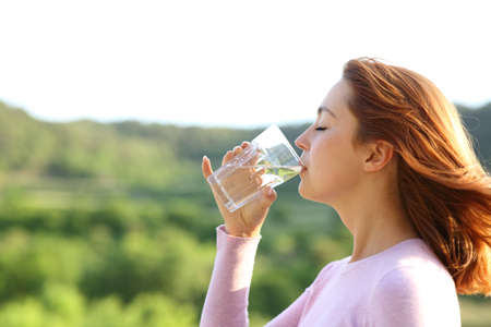 Profile of a woman drinking water from glass outdoor in nature