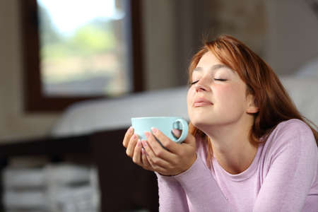 Woman relaxing breathing and holding coffee cup lying on the floor in the bedroom Archivio Fotografico
