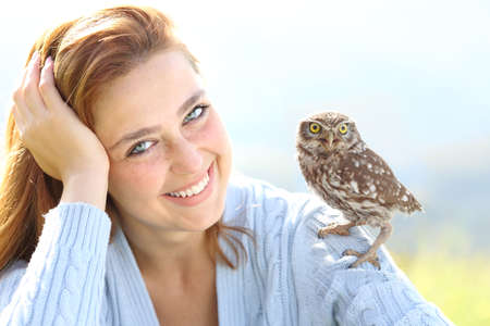 Beautiful woman with blue eyes posing with an owlet looking at camera