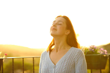 Satisfied woman is breathing fresh air in a balcony at home at sunset
