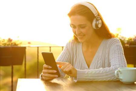 Happy woman weairng headphones listening to music checking smart phone in a balcony at sunset
