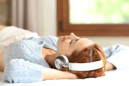 Relaxed woman resting lying on a bed listening to music with wireless headphones at home