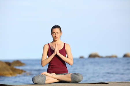 Front view full body portrait of a yogi practicing yoga pose on the beach