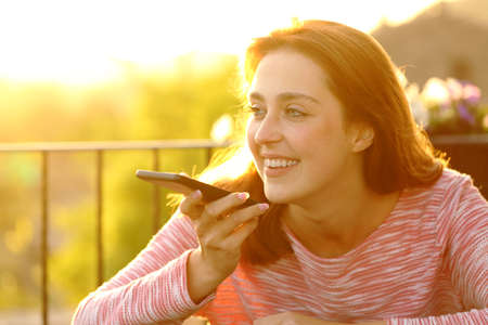 Happy female using voice recognition on smart phone at sunset in a balcony