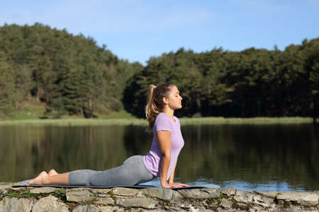 Side view portrait of a woman doing yoga pose in a lake a sunny day