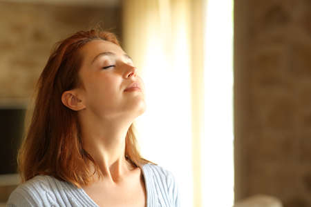 Redhead woman breathing fresh air in the living room at home