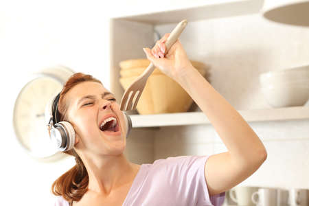 Happy woman listening to music with headphones singing using a fork as a microphone in the kitchen