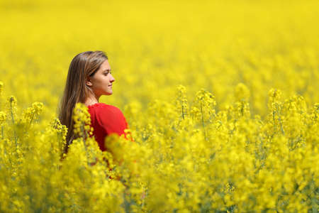 Woman in red contemplating in a yellow field in spring season