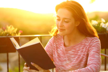 Relaxed woman reading a book in a balcony at sunset with a war light