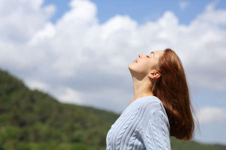Profile of a woman breathing fresh air in the mountain with a cloudy sky