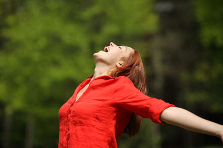 Happy woman in red screaming to the air stretching arms in a forest or park