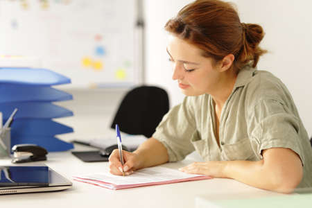 Relaxed woman working filling paper form on a desk at office