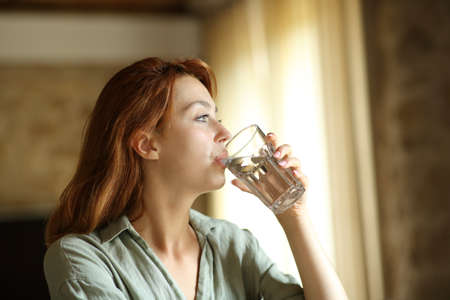 Woman drinking water from glass sitting at home or apartment Archivio Fotografico