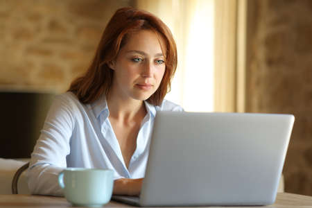 Concentrated freelancer woman working with laptop at home