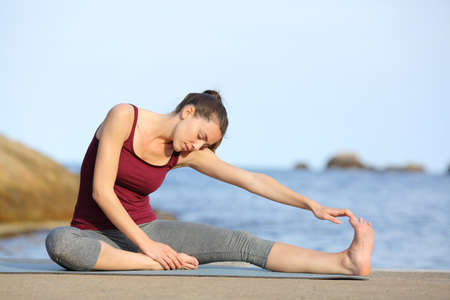 Full body portrait of a sportswoman stretching leg after sport on the beach Archivio Fotografico