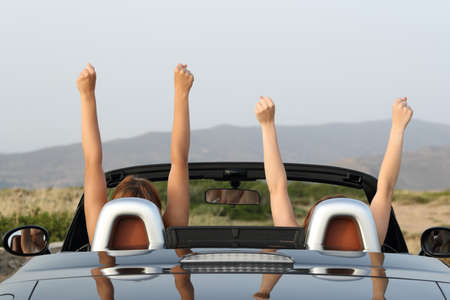 Back view portrait of two women raising arms in a convertible car enjoying views in the mountain