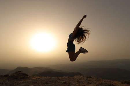 Side view portrait of a woman silhouette jumping at sunset in the mountain Archivio Fotografico