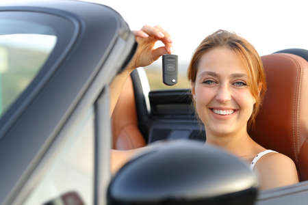 Happy convertible car owner showing keys to camera