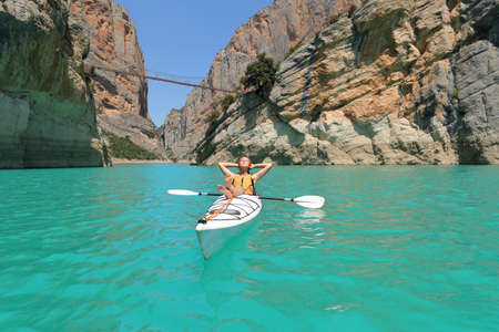Relaxed woman resting in a kayak in a beautiful lake on summer vacation Archivio Fotografico