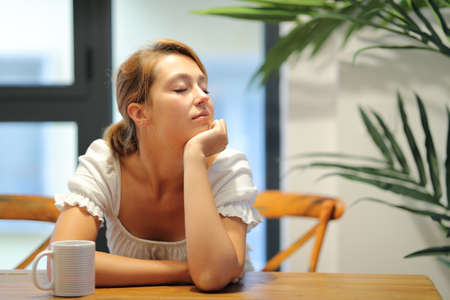 Woman resting sitting in a table at home with closed eyes