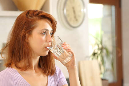 Serious woman drinking tap water looking away in the kitchen Archivio Fotografico
