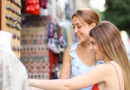Two happy friends buying souvenirs in a store in the street on vacation Archivio Fotografico