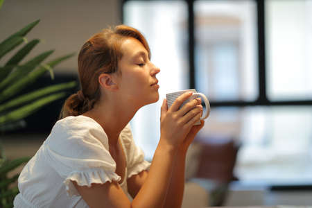 Profile of a relaxed woman smelling coffee cup sitting at home Archivio Fotografico
