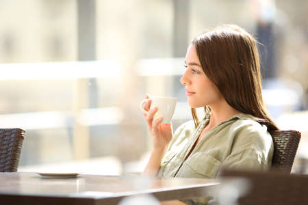Side view portrait of a relaxed woman contemplating views drinking coffee in a bar