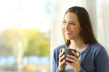 Happy pensive woman looks at side beside a window holding a coffee cup at home
