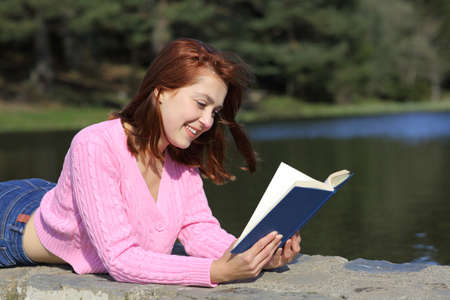 Happy woman reading a paper book lying in the mountain
