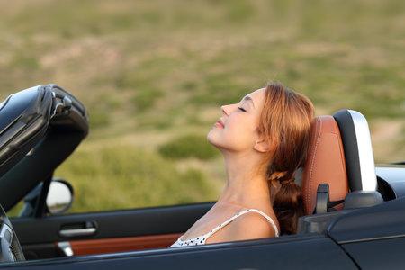 Profile of a woman breathing fresh air in a convertible car Archivio Fotografico