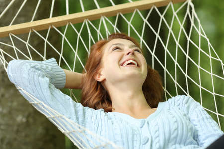 Happy woman laughing lying on rope hammock in a forest Archivio Fotografico