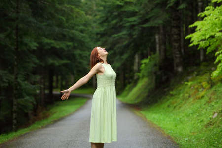 Happy woman smiling breathing fresh air in the mountain road Archivio Fotografico