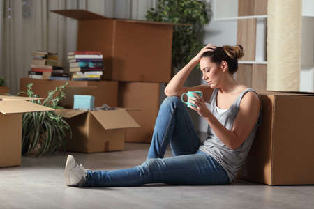 Sad evicted woman moving home complaining sitting on the floor in the night
